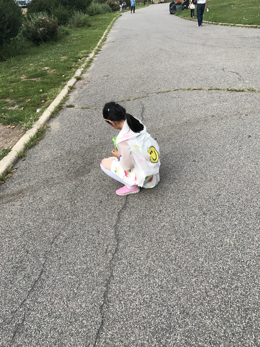 A girl crouches on a park path, looking down. Photographed from behind, we can not see what she sees on the path. She wears a white jacket with a yellow smiley face on the back, a white dress or skirt printed with red and green, white tights or tall socks with bows at the knee and baby pink sneakers.