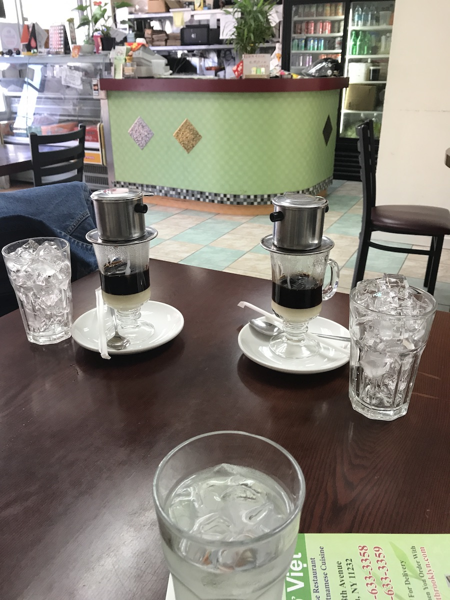 Five cups on a table in a restaurant. 3 x hexagonal beer glasses full of ice. 2 x Irish coffee glasses topped with a metal percolator dripping coffee onto a layer of sweetened condensed milk. These two glasses are placed on a small white plate that also holds a straw and a spoon. Front counter and drink fridge in the background.