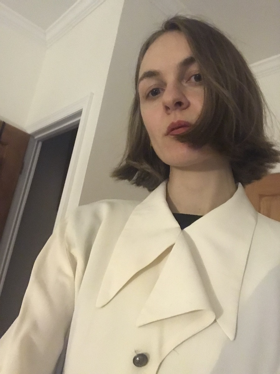 Selfie from below. Hair cut in bob to jawline. Wearing cream poet-type blouse with large wing collar.