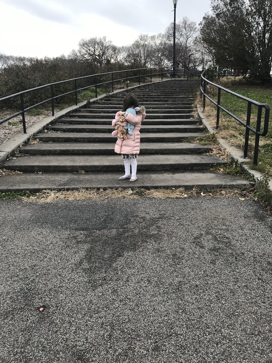 A girl wearing a pink puffer jacket with fur collar, white tights and flats is pictured at the bottom of a concrete stairwell in a park holding her toys, which obscure her face.