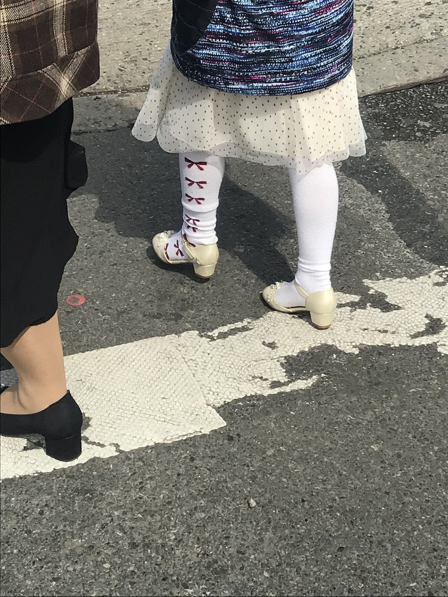 A child's legs wearing white tights with red bows along the side, white heeled church shoes, a glittery white skirt and multi-coloured striped jacket are walking across a crosswalk. Fragment of legs beside wearing sensible black pumps, long black skirt, brown tartan coat.