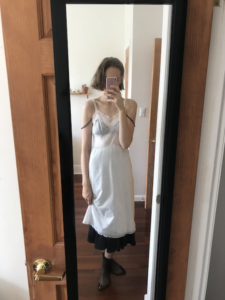Mirror selfie wearing black mesh ankle socks, long black skirt and black bra with straps hanging down, and semi-sheer white cotton slip dress layered over top.