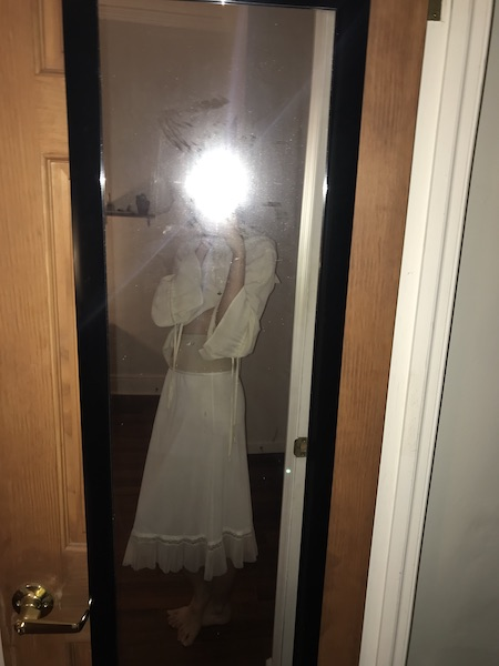 Mirror selfie with flash obscuring face posed a breath before sideways. Barefoot and wearing white slip skirt, nude girdle shorts pulled high, poets blouse pulled up at front.