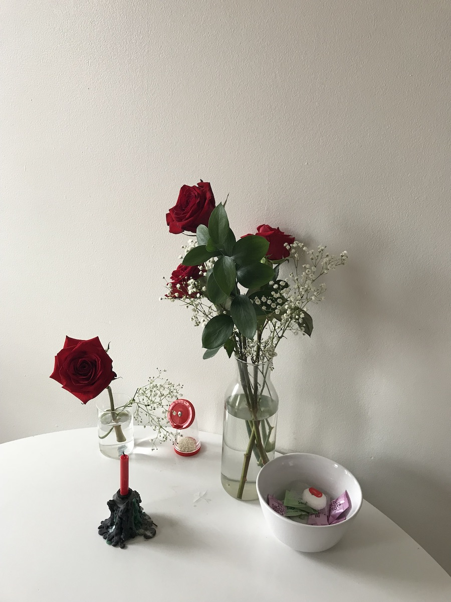 Red roses, candle, candies on a white tabletop.