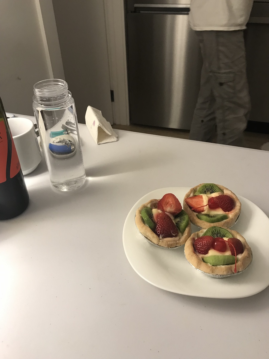 Three fruit custard tarts arranged on a white plate on a white table. Wine and water bottles, mug, napkin or paper are also on the table. Legs in grey cargo pants walk through the background.