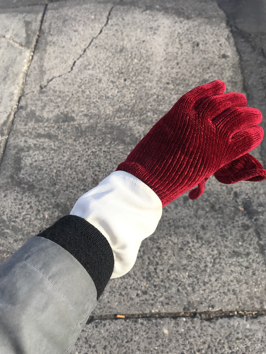 Photographed from above against concrete sidewalk, an arm from elbow down wearing grey jacket, black wool cardigan, cream cinched poets blouse, red glove.