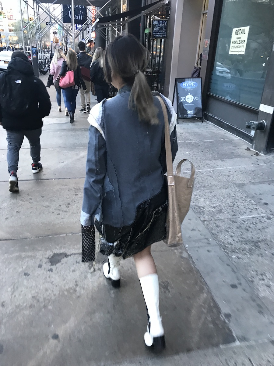 Photographed from behind, a person walks down a busy street wearing white go-go boots, a deconstrcuted denim skirt and jacket with a long black fishnet sleeve hanging down past the jacket's cuff.