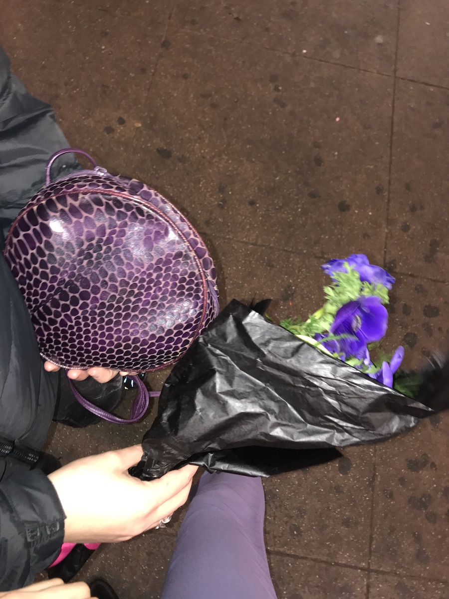 Photographed from above against a dirty subway platform, someone holds a purple handbag and bouquet of purple flowers wrapped in black paper. A purple pant leg is also visible.