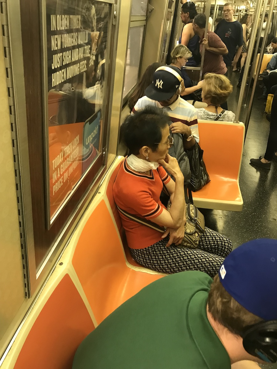 On a NYC subway car with orange seats, a person wears a generic plastic shopping bag as a scarf.