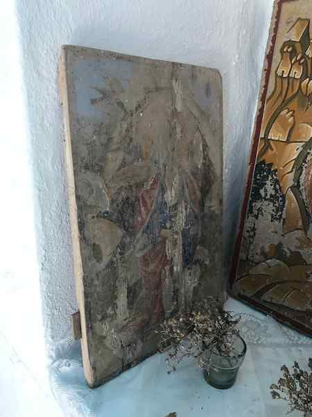 A very faded painting behind a small vase of dried thyme in a Greek country church