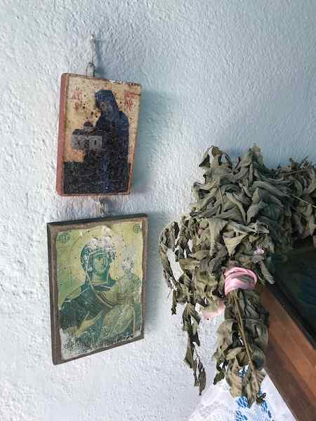 Two small icon paintings hung on wall beside a bundle of dried leaves in a Greek country church