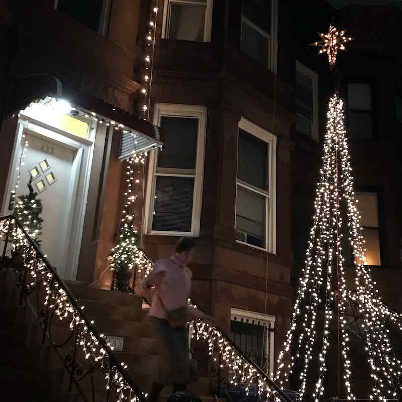 Photo by K of me running down old stoop at night with fairy lights all around