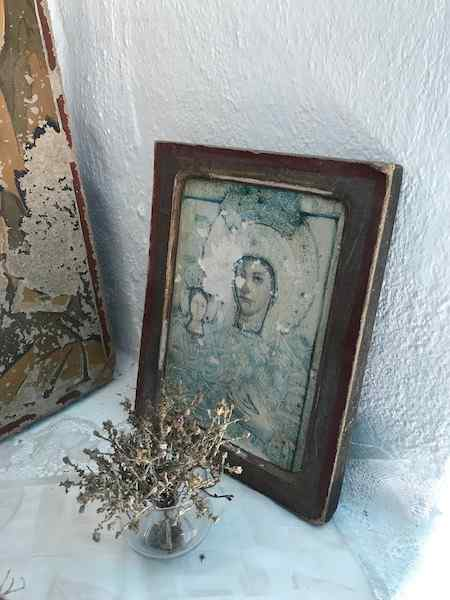 A worn icon painting behind a small vase of dried thyme in a Greek country church