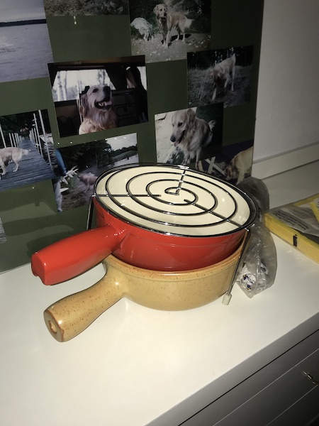 One red and one yellow nordic style fondue saucepans stacked with a wire rack on top