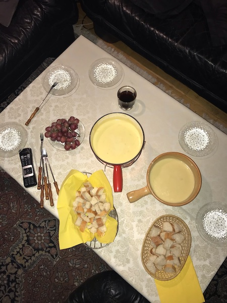 A spread of full fondue pans, bread baskets, purple grapes, drinking glasses and clear glass plates arranged on a low table photographed from above