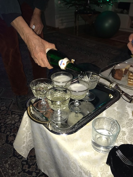 Champagne coupes on a tray with a hand coming in from the back of the frame filling them from a green bottle