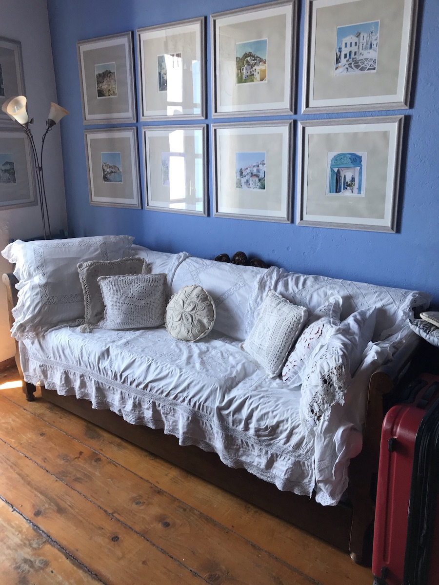 A couch covered in white blanket and pillows in front of a blue wall covered in framed watercolours