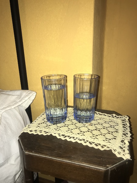 Two blue water glasses on a side table